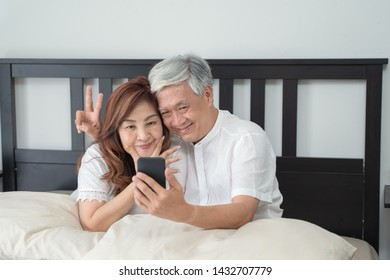 Happy Asian Senior Couple  lifestyle technology device concept,Lovely elderly couple take a selfie with by they smartphone