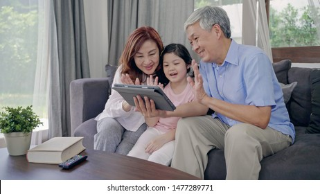 Happy Asian Senior Couple  lifestyle and family,Grandparents with her granddaughte Video Conferencing by tablet