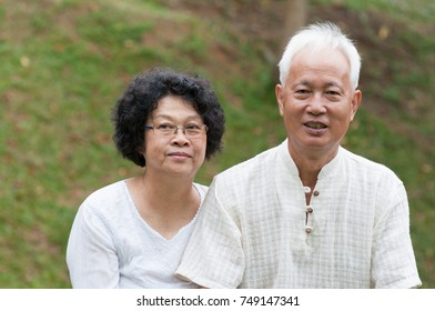 Happy Asian senior couple relaxing at outdoor park on a summer day.
