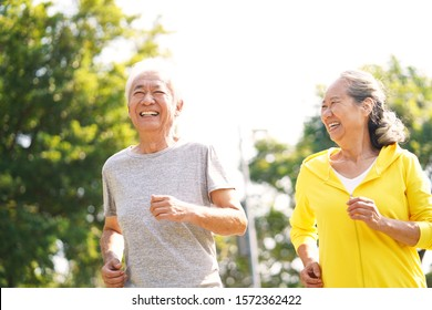happy asian senior couple running exercising outdoors in park