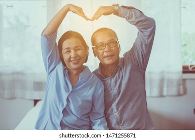 Happy asian senior couple showing hands heart shape together,Happy and smiling,Positive thinking