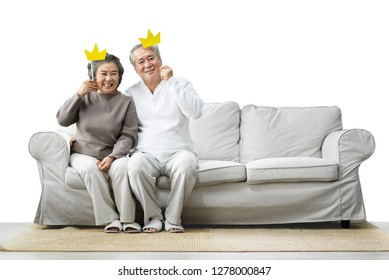 Happy Asian Senior Couple sitting on sofa while holding yellow paper crowns on sticks and looking to camera at with clipping path on white background. Copy space. Funny, Laughing Feeling. Retirement.