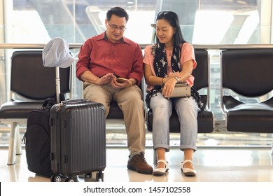 Happy asian senior couple sitting on bench using smart phone waiting for departure at  terminal airport . Elderly Journey. older lovers  wife and husband . travel. flight. retired . together. vacation