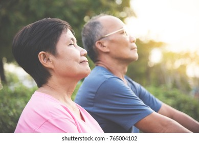 Happy Asian senior couple smiling and breathing fresh air while exercising at park outdoor.