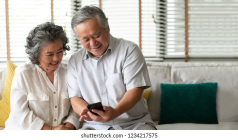 Happy Asian senior Couple using smartphone technology while smiling and sitting on couch at their home. Copy space.