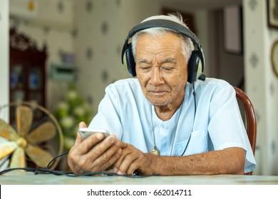 Happy asian senior man Headphones Listening Music at home