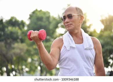 Happy Asian Senior man wear sunglasses exercising with lifting dumbbell at park outdoor.