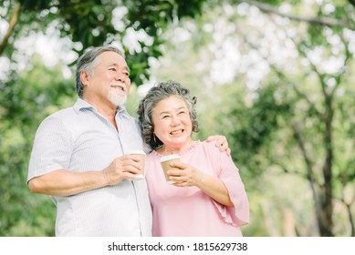 Happy Asian senior older couple drink coffee together outdoor in park