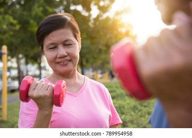 Happy Asian Senior people exercising with lifting dumbbell at park outdoor together.