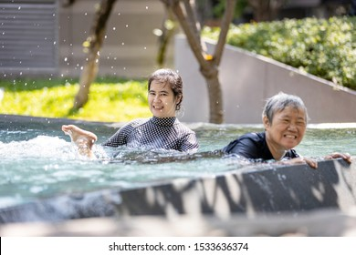 Happy asian senior people and young woman having fun,enjoy together in swimming pool,healthy elderly mother exercising,learns to swim in pool with smiling trainer or daughter, health care concept