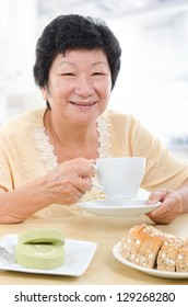 Happy Asian senior woman having breakfast at home