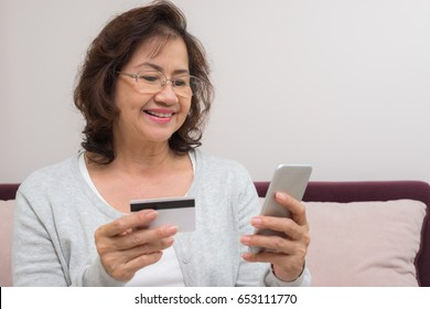 Happy Asian senior woman shopping online pay with credit card