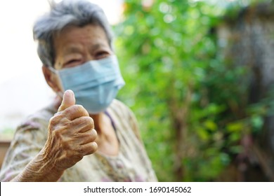 Happy Asian senior woman shows thumb up for fighting with COVID-19 by wearing hygiene mask with blurred face background, hand close up, coronavirus protection concept