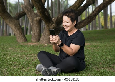 Happy Asian Senior woman using smart phone  in the park.