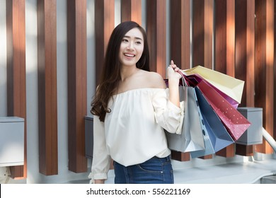 happy asian shopaholic woman with colorful shopping bags at department store shopping mall