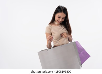 Happy asian shopping woman stand,hold shopping bags on white blackground.She enjoy in lifestyle shopping on line concept,in midnight sales and discount on sales with laptop.
