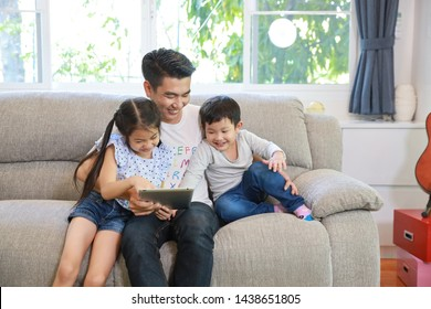 happy asian single dad teaching his daughter and son to use or play tablet on grey sofa in living room with laughing and smiling face (lifestyle with technology concept)