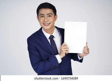 Happy Asian smiling young business man holding blank white small board, isolated on white background, asian model
