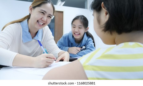 Happy Asian student girls studying with teacher in classroom