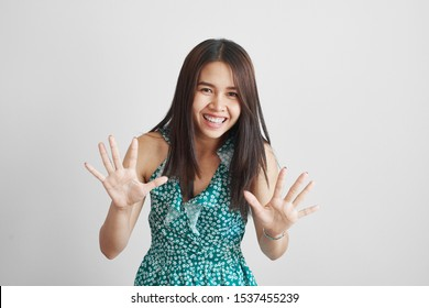 Happy Asian Thai girl in a green summer dress shows ten fingers and laughs joyfully isolated on a white background, asks to stop