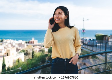 Happy Asian tourist laughing during international smartphone conversation, cheerful hipster girl visiting overlooking landscape and ucing roaming 4g for making mobile communication and discuss trip - Shutterstock ID 1896907960
