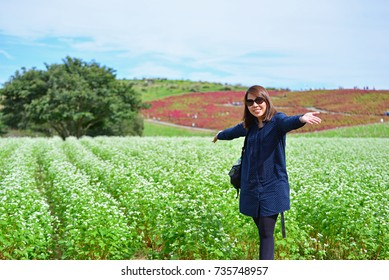 Happy Asian tourist woman in the field of Kochia at Hitachi Seaside Park in Hitachinaka, Ibaraki, Japan. Nature Background during autumn season. Concept about happiness journey
