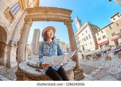 Happy asian tourist woman with map lost in old town of Montepulciano, Tuscany. Vacation and travel in Italy concept