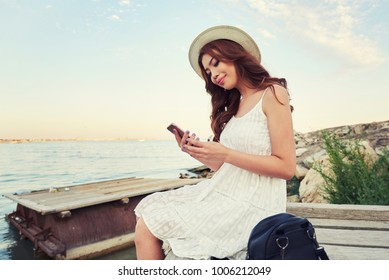 Happy  asian woamn having pleasant mobile phone conversation with friend while sitting near ocean. Girl using cellphone near the river in sunrise sunset.