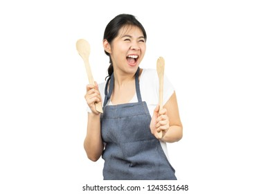 Happy Asian woman in apron enjoy cooking with wooden spoon and fork isolated on white background