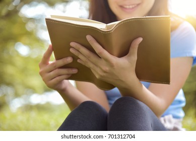 Happy Asian woman in Blue shirt reading a book on Green natural background. Girl is smiling at Outdoor park. Copy space.