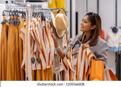 Happy Asian woman choosing clothes in shop store with happy action at department center