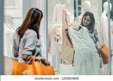 Happy Asian woman choosing clothes with reflection of glass in shop store shop with happy action at department center