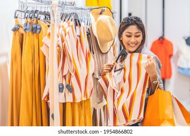 Happy Asian woman choosing clothes in glass store shop with happy action at department center, shopping and shopaholic, lifestyle fashion and leisure, sales and black friday concept