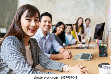 Happy asian woman and creative team are smiling and looking at camera in modern workspace office. Happy group of confident employee in cowork. Relation and engagement concept.