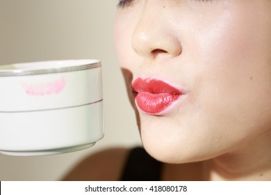 A happy Asian woman with a cup of coffee