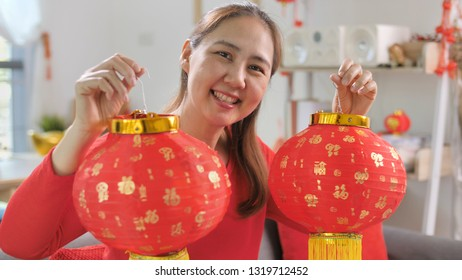 Happy Asian woman decorate her house for Chinese New Year Celebrations