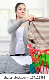 happy asian woman doing the laundry at home