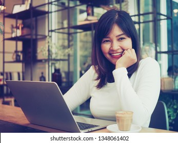 Happy Asian woman drinking coffee and working in coffee shop