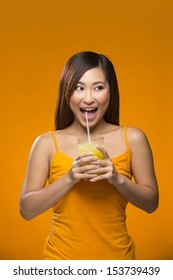 Happy Asian Woman drinking orange juice on a colorful background. Healthy living concept. Young and fresh Asian female model an orange background.
