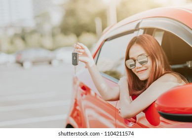 Happy Asian woman driver holding car key in her new car