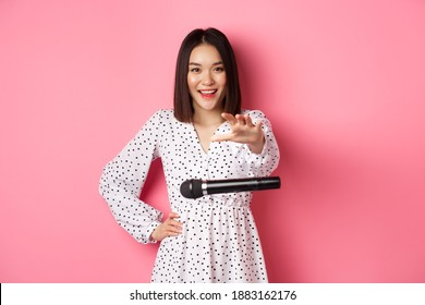 Happy asian woman drop the microphone, smiling and looking confident at camera, standing over pink background