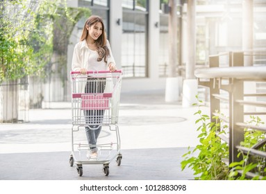 Happy Asian woman with empty shopping cart ready to shopping