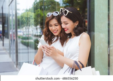 Happy asian woman friends holding bags with purchases, smiling while looking at phone in shopping center.