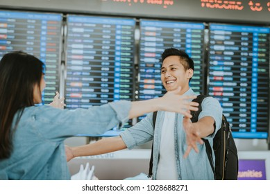 Happy Asian woman giving warm welcome hugging to her boyfriend after he return from abroad at an airport
