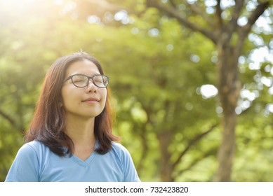 Happy Asian woman with Glasses in Blue shirt breathing deep fresh air on Green natural background. Girl with Outdoor park. Copy space.