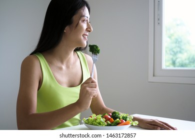 A happy Asian woman with a healthy salad dish, holding fork with a large broccoli. Food for good shape