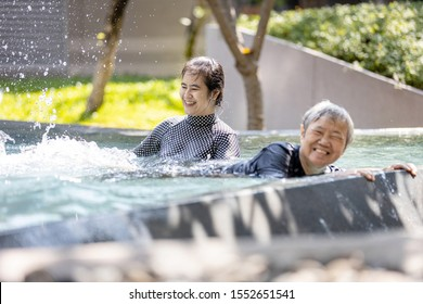 Happy asian woman help, care senior people in swimming pool,healthy elderly mother exercising,learns to swim in pool with smiling trainer or daughter in outdoor on sunny day,feeling relax,health care