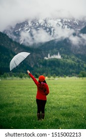Happy Asian woman hold umbrella in her hand standing in the meadow with background of green mountain and neuschwanstein castle. Concept of carefree, happiness, positive, joyful.