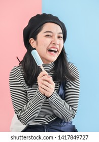 Happy Asian woman holding blue ice cream stick with color background.