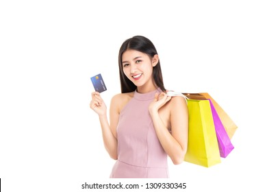 Happy asian woman holding shopping bags and credit card. Beautiful charming woman with many shopping bags brand name product that shop has discount isolated on white background. Copy space.